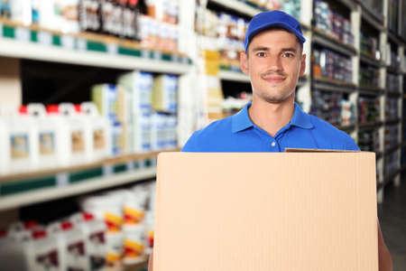 Man wearing uniform with cardboard box in store. Wholesale market