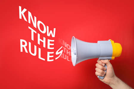 Man using megaphone to say Know the rules on red background, closeup