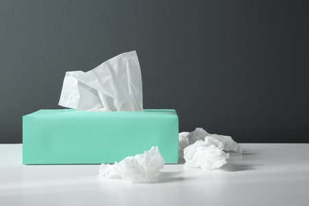 Used paper tissues and box on white table Stock fotó