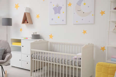 Stylish baby room interior with crib and decor elements Banque d'images