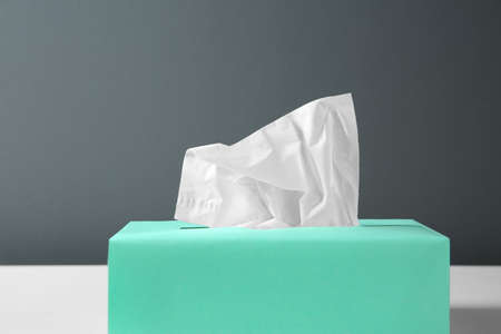Box with paper tissues on table against black background, closeup