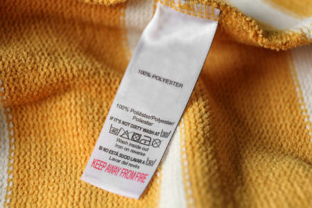 Clothing label with care symbols and material content on yellow shirt, closeup view
