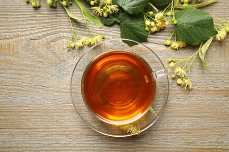 Cup of tea and linden blossom on wooden table, flat lay Stockfoto