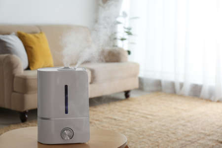 Modern air humidifier on wooden table indoors. Space for text