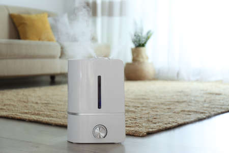 Modern air humidifier on floor indoors. Space for text