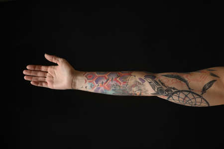 Woman with colorful tattoos on arm against black background, closeup Фото со стока