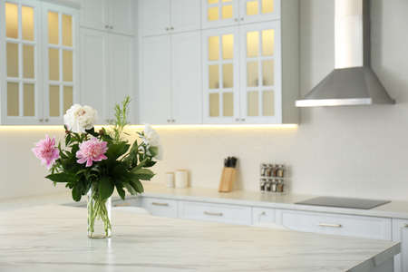 Peony bouquet on white marble table in kitchen interior Фото со стока