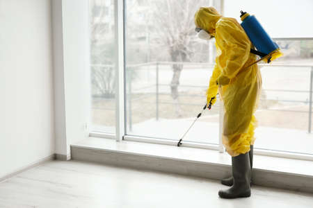Pest control worker in protective suit spraying pesticide near window indoors
