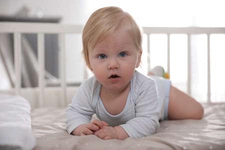 Adorable little baby lying in comfortable crib