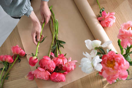 Florist making beautiful peony bouquet at table, top view