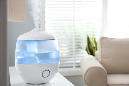 Modern air humidifier on table at home. Space for text