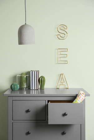 Grey chest of drawers near light wall in room Archivio Fotografico