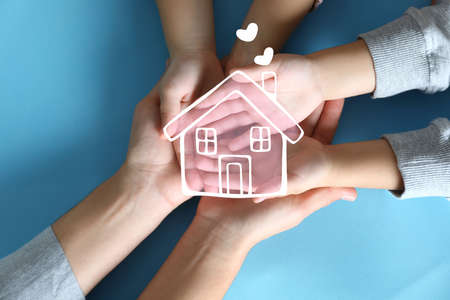 Illustration of house and happy family holding hands on blue background, top view Foto de archivo