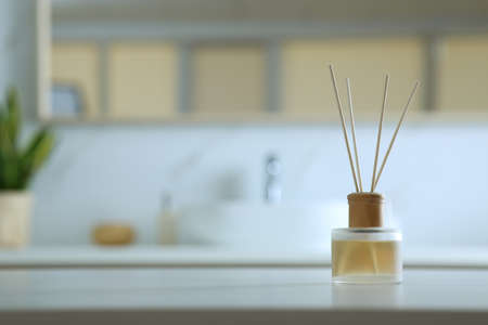 Aromatic reed air freshener on table indoors. Space for text
