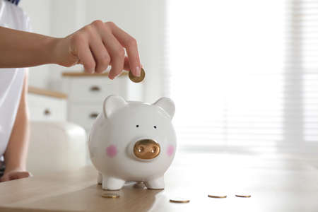 Woman putting money into piggy bank at wooden table indoors, closeup. Space for text Standard-Bild