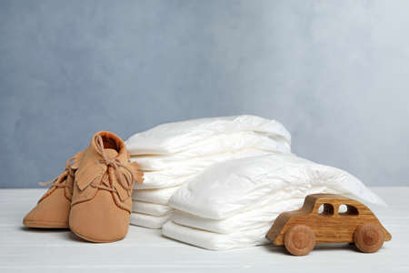 Baby diapers, child's shoes and toy car on white wooden table against grey background Banque d'images