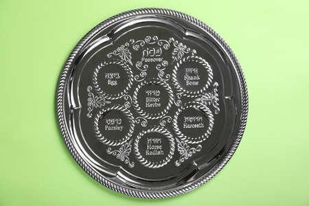 Passover Seder plate (keara) on light green background, top view. Pesah celebration