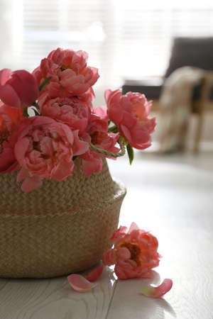 Beautiful bouquet of fragrant peonies on floor indoors
