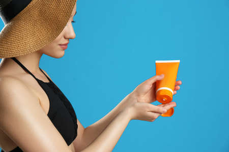 Young woman applying sun protection cream on blue background, closeup