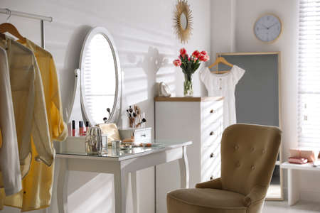 Stylish room interior with elegant dressing table and comfortable chair