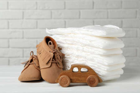 Baby diapers, toy car and child's shoes on wooden table against white brick wall