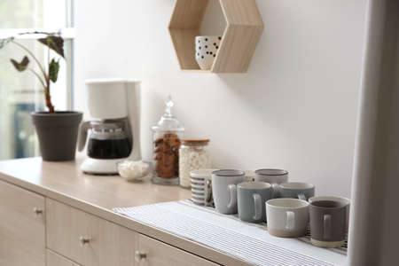 Modern coffeemaker and cups on commode near light wall indoors