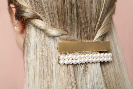 Young woman with beautiful gold hair clips on pink background, closeup