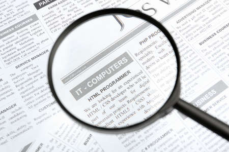 Looking through magnifying glass at newspaper, closeup. Job search concept