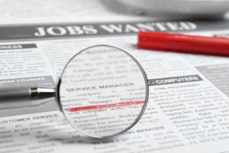 Looking through magnifying glass at newspaper, closeup. Job search concept Фото со стока