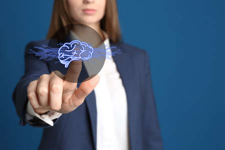 Woman pointing at digital image of brain on blue background, closeup. Machine learning concept  Reklamní fotografie