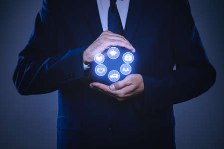 Businessman holding different icons on dark background, closeup. Insurance concept Stock Photo