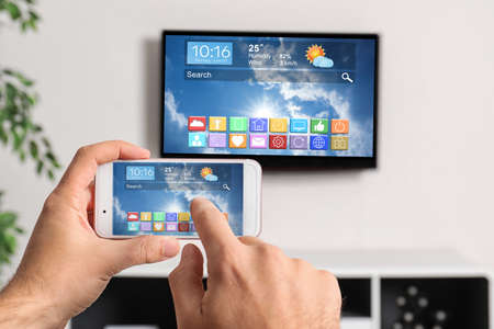 Man using phone connected to smart TV in living room, closeup Stock Photo