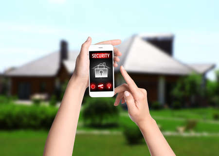 Woman monitoring modern CCTV cameras on smartphone near her house, closeup. Home security system Banque d'images