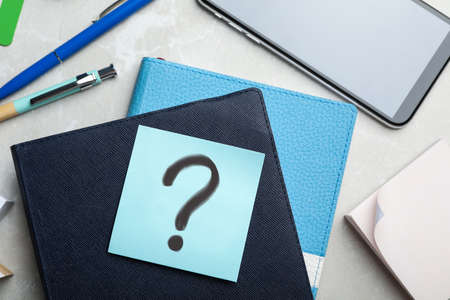 Reminder note with question mark and stationery on table, flat lay