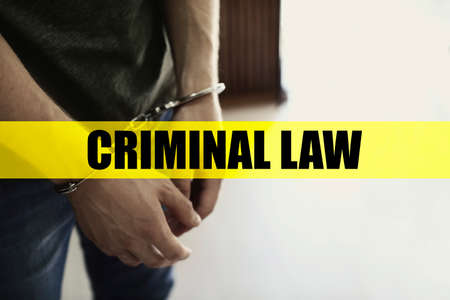 Man detained in handcuffs indoors. Criminal law concept