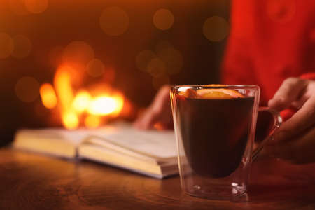 Woman with mulled wine reading book near fireplace indoors, closeup. Winter vacation