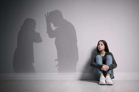 Upset teenage girl sitting on floor near wall and silhouettes of arguing parents Archivio Fotografico