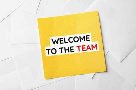 Note with phrase Welcome to the team on sheets of paper, top view