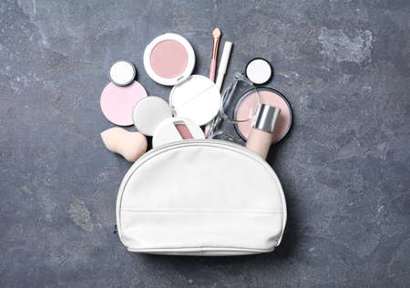 Cosmetic bag with makeup products and beauty accessories on grey stone background, flat lay Foto de archivo