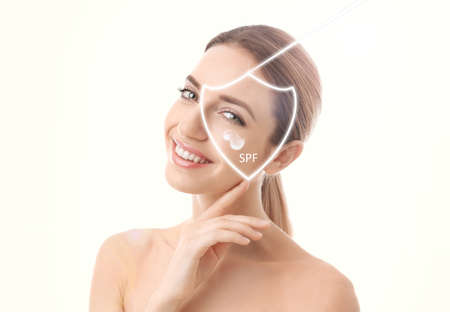 SPF shield and beautiful young woman with healthy skin on light background. Sun protection cosmetic product 免版税图像