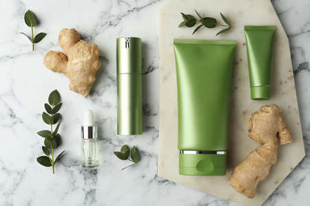 Set of cosmetic products, ginger and plants on white marble table, flat lay