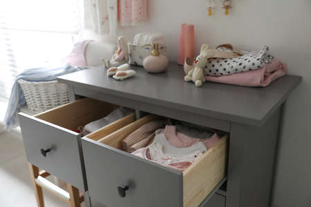 Open cabinet drawers with baby clothes in child room Stockfoto