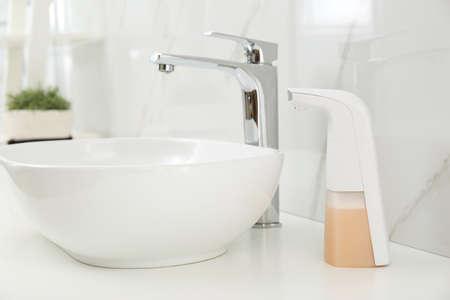Modern automatic soap dispenser near sink in bathroom, closeup