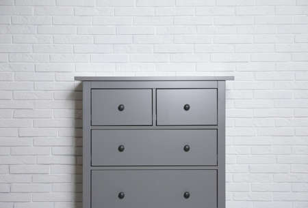 Grey chest of drawers near white brick wall indoors