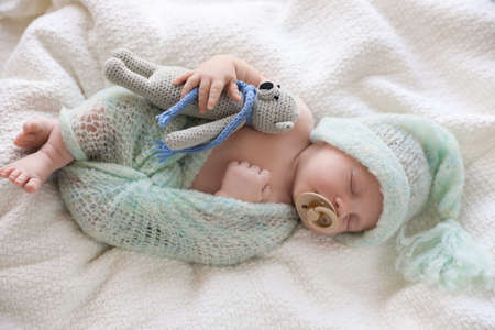 Cute newborn baby in warm hat with toy sleeping on white plaid, top view