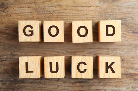 Cubes with phrase GOOD LUCK on wooden background, flat lay