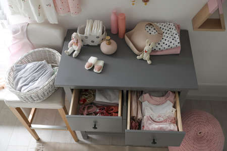Open cabinet drawers with baby shoes and clothes in child room