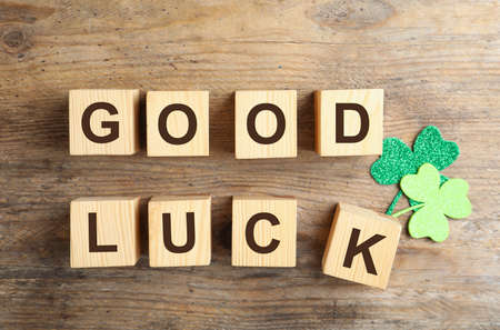 Cubes with phrase GOOD LUCK and clover leaves on wooden background, flat lay Reklamní fotografie