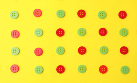 Many red and green sewing buttons on yellow background, flat lay