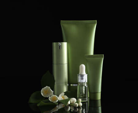 Set of cosmetic products and flowers on black background
